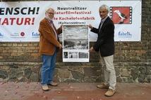 """Horst Conradt und Ulrich Meßner präsentieren stolz das Plakat des Gewinnerfilms """"Das Salz der Erde"""" © Barbara Lüthi-Herrmann, Nationalparkamt Müritz"""